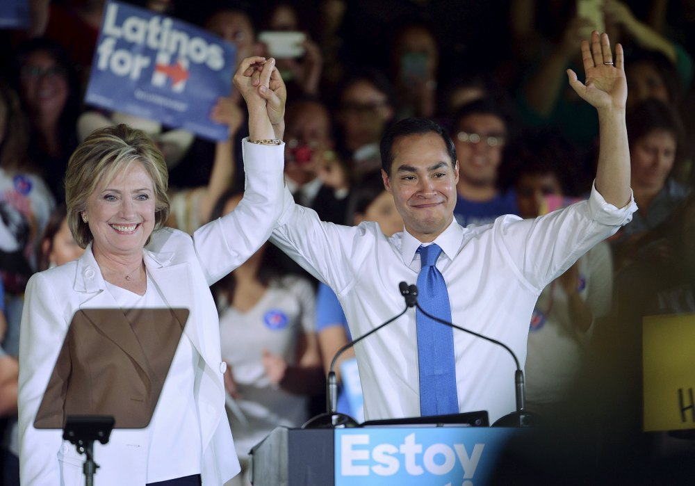 """File photo of Democratic U.S. presidential candidate Clinton holding the hand of HUD Secretary Castro after he endorsed her at a """"Latinos for Hillary"""" rally in San Antonio"""