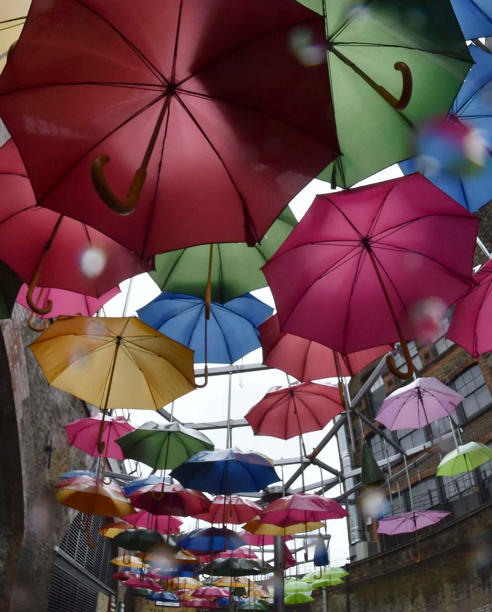 A sculpture constructed of umbrellas is seen in the rain in a street in central London